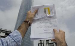 J. C. M. exhibe la sentencia ante la Torre Iberdrola de Bilbao, donde se encuentra la sede de Aenor